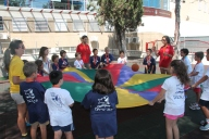 The monitors playing some games with the parachute in summer camp.